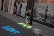 A woman wearing a striped dress walks through one of two patches of coloured light, created by nearby plate glass in central London.