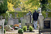 Nederland, Huissen, 3-11-2013Nabestaanden bezoeken een graf op een kerkhof, begraafplaats. Allerzielen, allerheiligen.Foto: Flip Franssen