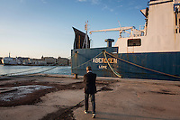 """TRAPANI, ITALY - 7 JUNE 2016: A marshal of the Guardia di Finanza (Financial Police) walks towards the cargo ship Aberdeen, seized in June 2014 as it was carrying 42 tons of hashish from Morocco to Libya, is docked here in the harbor in Trapani, Italy, on June 7th 2016.<br /> <br /> Between January 2014 e December 2015 more than 120 tons of hashish, carried on fishing boats or cargo ships from Morocco to Libya, were seized in the Strait of Sicily by Italy's Guardia di Finanza (Financial Police) thanks to an international police investigation named """"Operazione Libeccio"""", carried out by the GICO (Gruppo Investigativo Criminalità Organizzata, Organised Crime Investigation Group), a unit of the tax police of Palermo under the supervision of the DDA (Direzione Distrettuale Antimafia) of Palermo.<br /> <br /> """"What is happening in Libya is same historical occurrence that happened years ago in Afghanistan. Such as the Talibans who financed their terroristic activities with heroin trafficking for the purchase of weapons, the Caliphate is proposing the same terroristic strategy by purchasing and commercialising hashish in order to purchase weapons used in their war"""" Sergio Barbera, Deputy General Prosecutor of Palermo, said."""