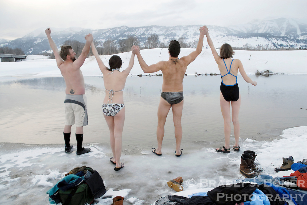 NEWS&GUIDE PHOTO / BRADLY J. BONER.Members of the fledgling Jackson Hole Polar Bear Swim Club, from left, Peter Keenan, Liza Beance, Mark Holloway and Katie Wilson join hands and give out a yell before taking a Valentine's Day dip in the Snake River on Tuesday evening. Holloway hopes to recruite more dunkers into the club, citing the activitie's invigorating benefits.