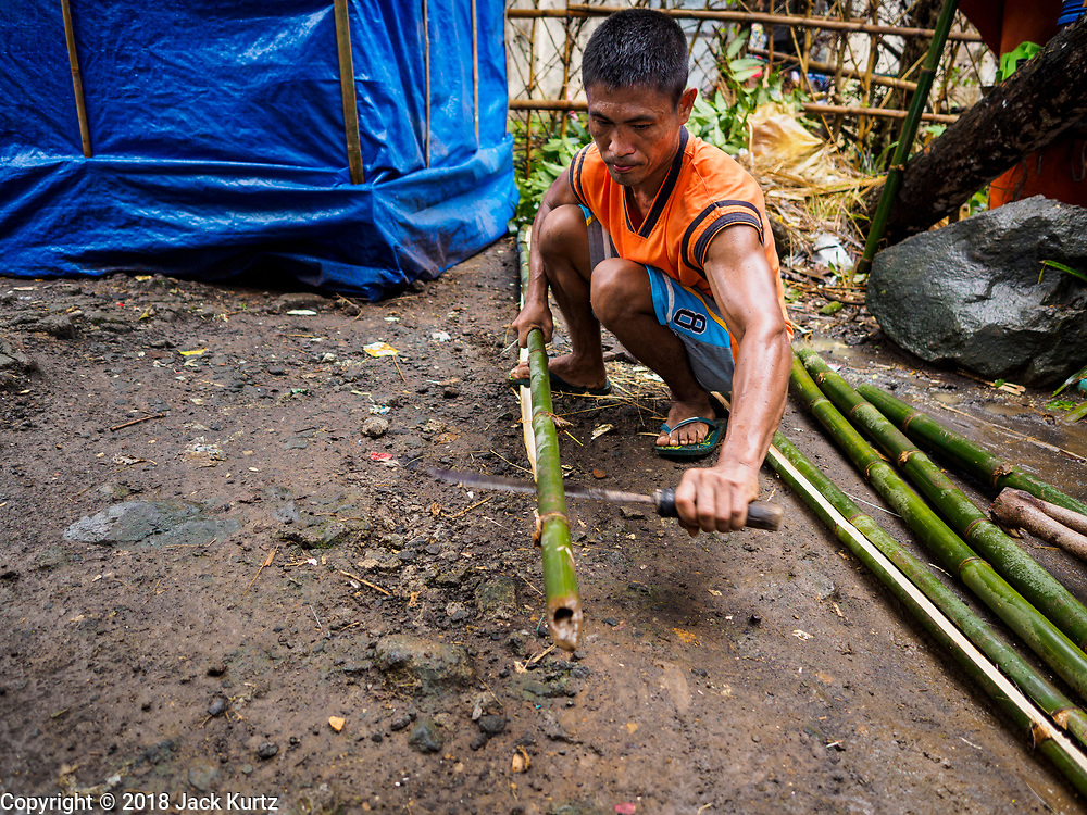 26 JANUARY 2018 - SANTO DOMINGO, ALBAY, PHILIPPINES: A man evacuated off the Mayon volcano splits bamboo for the hut he is building at Barangay Lidong shelter. The shelter is in school and all of the classrooms are already being used to house evacuees. Recent arrivals are living in tents on the school grounds. The volcano was relatively quiet Friday, but the number of evacuees swelled to nearly 80,000 as people left the side of  the volcano in search of safety. There are nearly 12,000 evacuees in Santo Domingo, one of the communities most impacted by the volcano. The number of evacuees is impacting the availability of shelter space. Many people in Santo Domingo, on the north side of the volcano, are sleeping in huts made from bamboo and plastic sheeting. The Philippines is now preparing to house the volcano evacuees for up to three months.      PHOTO BY JACK KURTZ
