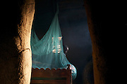 A mosquito net above a bed in a traditional mud hut in Kisii, Kenya.