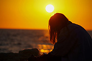 Silhouette of young woman on the beach at sunset. Photographed on the Tel Aviv Beach, Israel in March