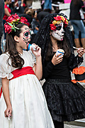 Young girls dressed in La Calavera Catrina costumes eat ice cream during the Day of the Dead or Día de Muertos festival October 31, 2017 in Patzcuaro, Michoacan, Mexico. The festival has been celebrated since the Aztec empire celebrates ancestors and deceased loved ones.
