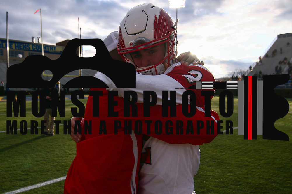 emotional Smyrna quarterback Nolan Henderson (2) hugs a coach after winning the DIAA division one Football Championship game between Top-seeded Middletown (11-0) and second-seeded Smyrna (11-0) Saturday, Dec. 03, 2016 at Delaware Stadium in Newark.
