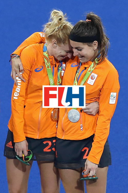 RIO DE JANEIRO, BRAZIL - AUGUST 19:  Margot van Geffen #23 (L) and Eva de Goede #24 of Netherlands react on the podium after winning silver medals in the Women's Hockey Final match against Great Britain on Day 14 of the Rio 2016 Olympic Games at the Olympic Hockey Centre on August 19, 2016 in Rio de Janeiro, Brazil.  (Photo by Mark Kolbe/Getty Images)