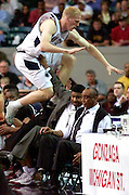 Penn State University forward Tyler Smith leaps high over the Temple Bench and Owls coaches Nate Blackwell (with arm up) and head coach John Chaney during action in the NCAA South Regional in Atlanta, Georgia March 23, 2001. The winner of the game will face Michigan State for a trip to the Final Four.