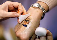 A Berkshire Hathaway shareholder has a temporary tattoo of BH Chairman Warren Buffett applied to her hand at the company trade show during the BH annual meeting in Omaha, Nebraska April 30, 2011. Dozens of BH companies had displays in the building next to the site of the meeting.  REUTERS/Rick Wilking  (UNITED STATES)