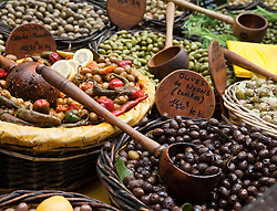 An enormous variety of olives, vintage clothing, toys, and antiques share sidewalk space with amazing food and working artists during the Sunday flea markets for which the town of L'Isle-sur-la-Sorgue is famous.