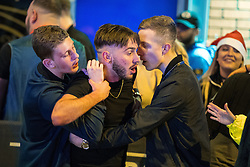 """© Licensed to London News Pictures . 24/12/2016 . Manchester , UK . Two men hold a third back during a scuffle . Revellers out in Manchester City Centre overnight during 2016's second """" Mad Friday """" , named for historically being one of the busiest nights of the year for the emergency services in the UK . Photo credit : Joel Goodman/LNP"""