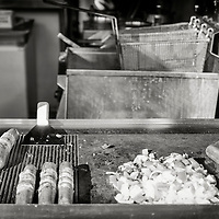 """On Hollywood Blvd a small restaurant serves street-style hot dogs straight of a grill on the sidewalk. The bacon-wrapped hotdogs topped with grilled onions and peppers are commonly sold by street vendors in Los Angeles, especially late at night outside concert venues and clubs. They're fondly known as """"dirty dogs"""" or """"danger dogs."""""""
