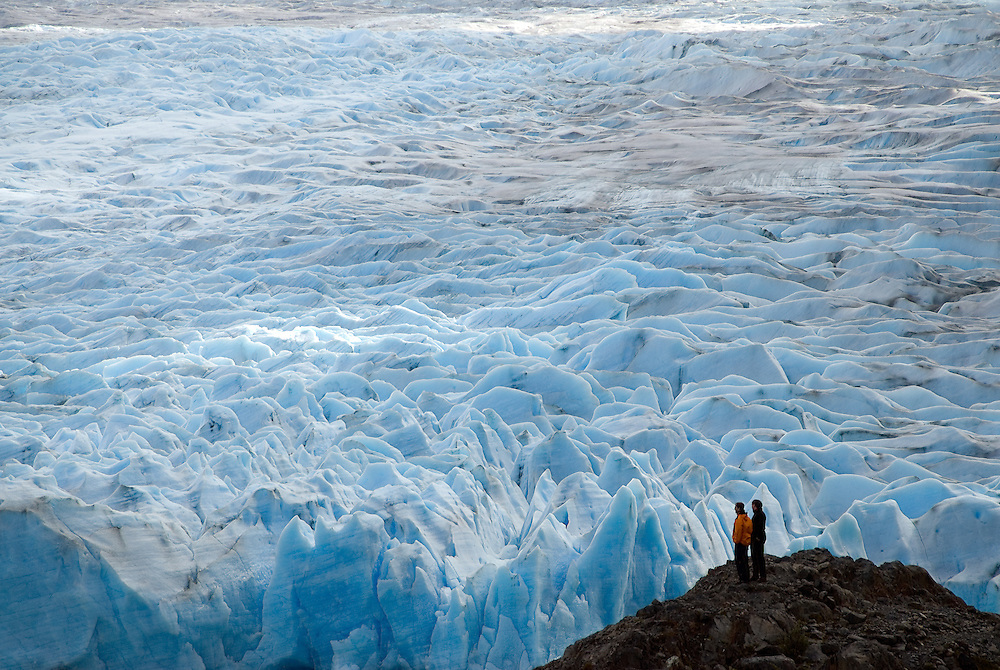 Hikers gazing out at the Grey Glacier in Torres Del Paine National Park, Patagonia, Chile.