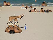 sunbathers one by himself lying on the beach Miami USA