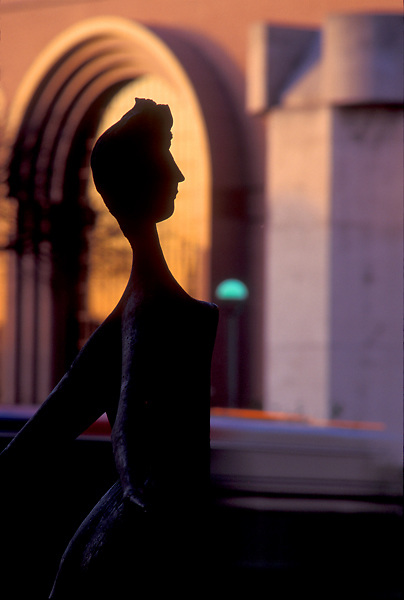 Stock photo of the silhouette of a sculpture against the sun setting on the Wortham Center, Houston, Texas