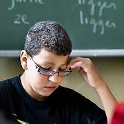 Nederland Rotterdam 23-09-2009 20090923 Serie over onderwijs, openbare scholengemeenschap voor mavo, havo en vwo.  lesuur nederlandse taal,  leerling maakt klassikaal oefeningen. Op de achtergrond werkwoordvormen op het schoolbord.                                                   .Foto: David Rozing