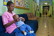Margaret, a female carer at Door of Hope Children's Home sits in the waiting room corridor playing with 6 month old baby Jesse. They are waiting for Jesse to have a routine medical examination as part of the adoption process.  The check-up is provided by Bigshoes Foundation, a charity that provides medical care to children living in children's homes and those who have been adopted.