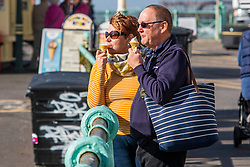 © Licensed to London News Pictures. 12/10/2016. Brighton, UK. A couple enjoys and ice cream in the sunshine on the Brighton and Hove promenade. Photo credit: Hugo Michiels/LNP