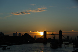 © Licensed to London News Pictures. 10/10/2014. London, UK. An orange sunrise over Tower Bridge on the River Thames in London is seen with clear blue sky and fine weather this morning. Photo credit : Vickie Flores/LNP