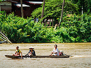 18 JUNE 2016 - DON KHONE, CHAMPASAK, LAOS: A Lao family guides their canoe up the Mekong River past guest houses on Don Det. Don Det and Don Khone Islands, are two of the larger islands in the 4,000 Islands chain on the Mekong River in southern Laos. They become a backpacker hot spot, there are lots of guest houses and small restaurants on the north end of the island.     PHOTO BY JACK KURTZ