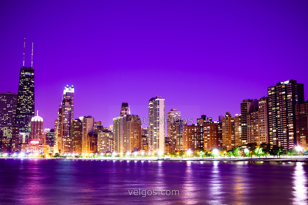 Photo of Chicago at night with a purple sky. Includes the famous John Hancock Center skyscraper one of the tallest buildings in the world. Photo is large high resolution and was taken in 2012.