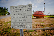 Edison Darder a life long residents' sign on Ise de  Jean Charles next to a survial pod from an oil rig. He wont move off the island though it is no longer safe  during a storm. The threat of flooding is high and inevitable when hurricanes come near the area. The island is eroding steadily and will no longer be habitable in the near future.