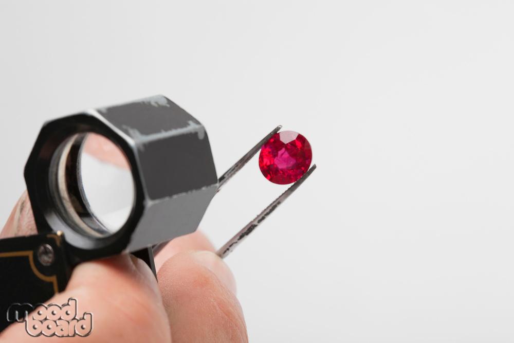 Close up of red gemstone in tweezers