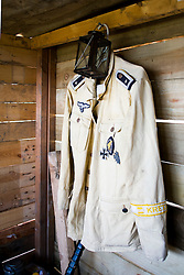"""German Fallschirmjäger feldwebel tropical jacket hangs in a camouflaged bunker . The Feldwebel rank has no British Equivalent but would sit between a Colour Sergeant and Sergeant Major. The breast eagle is that of the Luftwaffe. On the left breast pocket is the Iron Cross first Class, War Merit Cross 1st Class and Luftwaffe Fallschirmjager qualification cloth badge. The left sleeve has the """"Kreta"""" cufftitle  The cufftitle which was awarded to personnel who made a parachute or glider landing onto the island of Crete between 20 and 27 <br /> 04 July 2015<br />  Image © Paul David Drabble <br />  www.pauldaviddrabble.co.uk"""