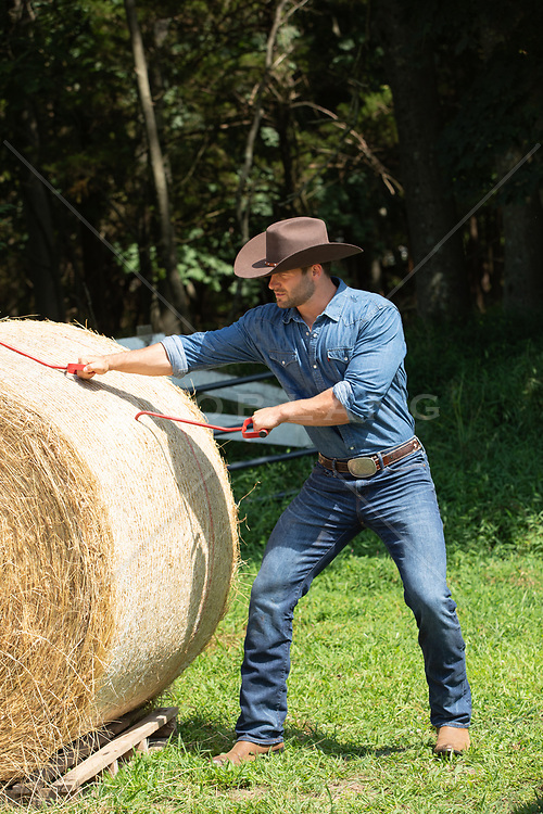 rugged cowboy working on a hay bale