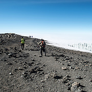 Climbers start the descent along a ridge from Uhuru Peak, the summit of Mt Kilimanjaro. A glacier is at right of frame.