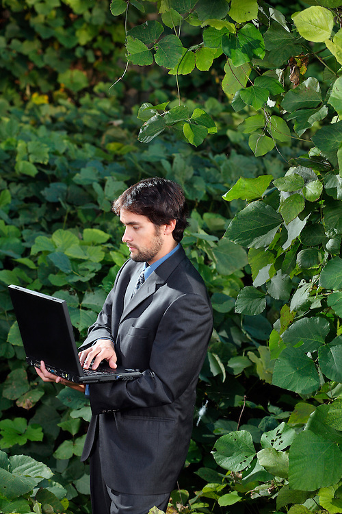 Davis M. with a laptop computer while surrounded by Kudzu Leaves