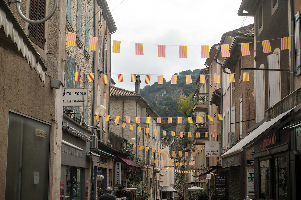 Colorful orange and yellow striped flags hang above a shaded shop lined street in the central district of Vaison la Romaine, in the Provence region of France. A 1st Century Roman bridge crosses the river Ouveze near the street.