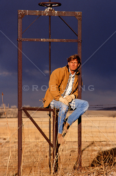 handsome and rugged blond haired man sitting on a metal fence in New Mexico