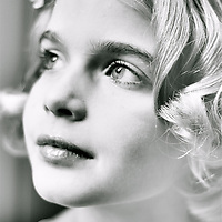 A young girl with blonde hair looking up in hope