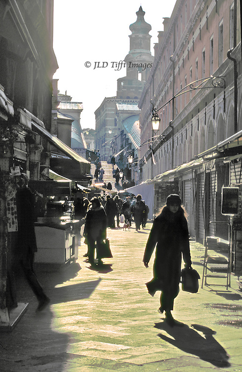 Morning shoppers at Rialto market, Venice; Rialto Bridge in background.  One woman in the foreground carries a bag, casts a full length shadow toward us..