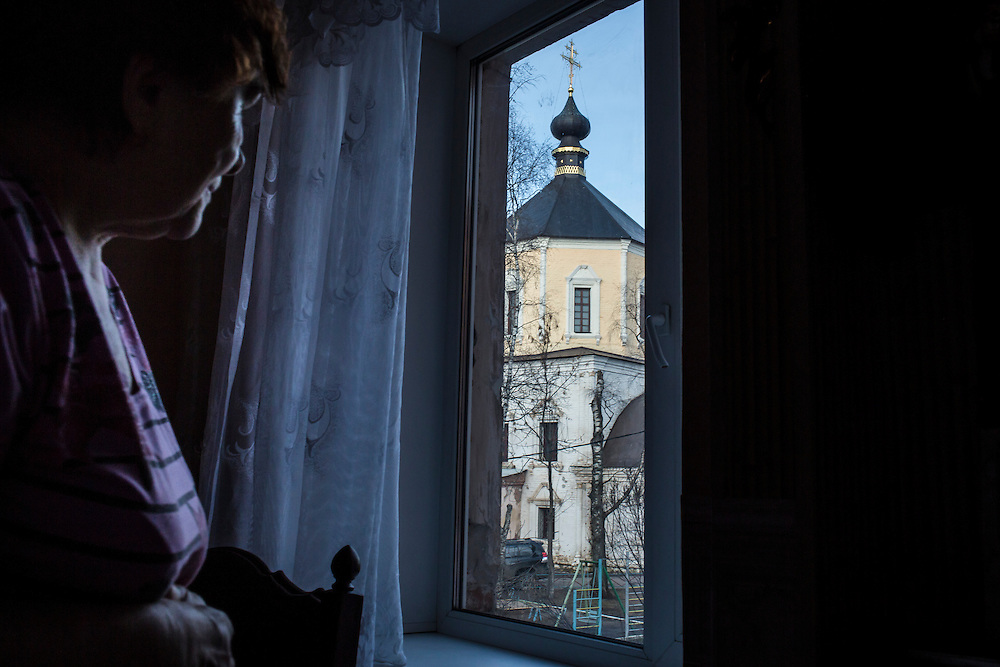 Nina Rozova, Alexander Panin's grandmother, looks out a window with a view to a nearby church in her apartment where Panin was mostly raised on Tuesday, February 25, 2014 in Tver, Russia. Panin, a Russian citizen who was arrested in the Dominican Republic in June 2013, is set to be charged by federal authorities in the US with being part of a gang which robbed bank accounts via the Internet. Photo by Brendan Hoffman, Freelance