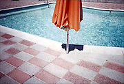 """Orange Umbrella"" and two other images from this series, plus a pool image from  ""California Ruins"" are included in Getty, 2011-2012 initiative ""Pacific Standard Time: Art in Los Angeles, 1945-1980"" for the Palm Springs Art Museum's ""Pacific Standard Time"" exhibition ""The Swimming Pool in Southern California Photography, 1945-1982"" opening January, 2012. http://www.pacificstandardtime.org. ""The Motel Series"" grew out of a portfolio on ""California Ruins"" that I ibrought to California Magazine, published in the Nov. 1982 issue. Once the magazine took over the direction of the ""Ruins"" Series, I began shooting a new group of images where I could have complete control again. ""The Motel Series"" was shot on Kodachrome 64 film, with my Olympus XA Camera, in Desert Hot Springs, CA. Later, these motels became chic ""spa retreats"" converted during the 1990's. A selection  of prints, from ""The Motel Series"" was gifted to the Palm Springs Art Museum, for their permanent collection, in 2002."