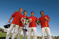 Four polo players with trophy