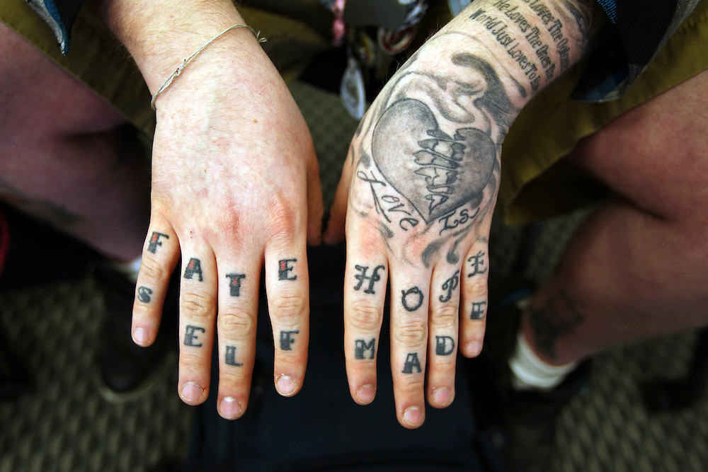"""3/7/11 5:25:28 PM -- Minneapolis, MN, U.S.A.---.StepUP program participant and addict-in-recovery James """"Bear"""" Mahowald, 21, of Hastings, MN, displays the tattoos on his hands at Augsburg College in downtown Minneapolis March 7, 2011.  He prefers to let people who notice his ink interpret the words and designs for themselves rather than explain what they mean to him..---.Photo by Courtney Perry, Freelance."""