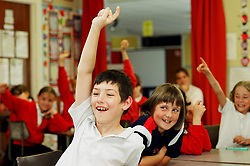 Children in class with their hands in the air; primary school; Yorkshire UK
