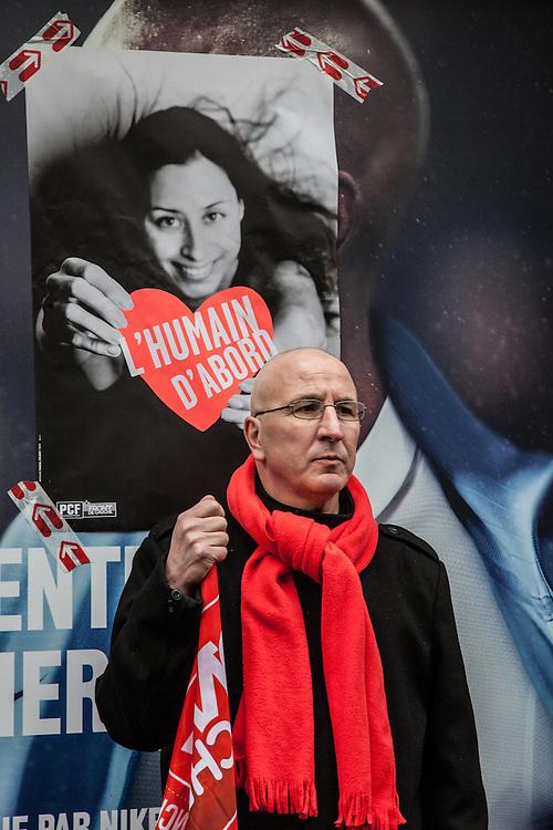 """Un homme portant une écharpe rouge se tient devant une affiche """"L'humain d'abord"""", à proximité de la place de la Bastille, lors de la manifestation du Front de Gauche le 18 mars 2012."""
