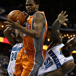 April 8, 2011; New Orleans, LA, USA; Phoenix Suns point guard Aaron Brooks (0) is defended by New Orleans Hornets center Emeka Okafor (50) and power forward Carl Landry (24) during the fourth quarter at the New Orleans Arena. The Hornets defeated the Suns 109-97.   Mandatory Credit: Derick E. Hingle