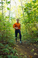 A man out trail running in a forested area<br />