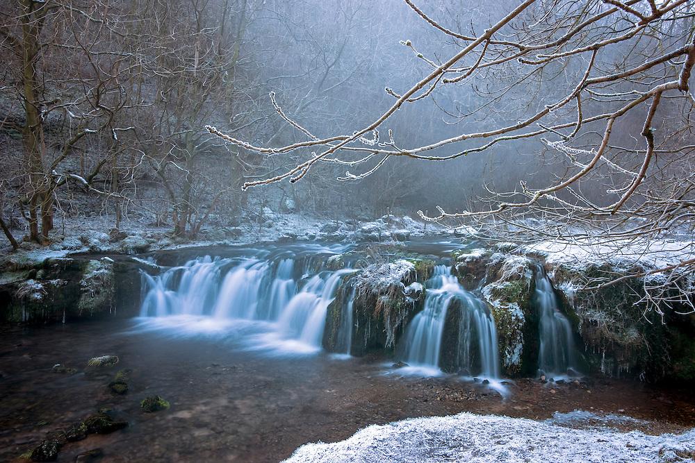 Lathkill waterfall in winter, Lathkill Dale, Peak District, UK