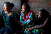 "Usha, 25, (left) and two other members of the Red Brigades are sitting inside Usha's home in Madiyaw colony, Lucknow District, Uttar Pradesh. The Red Brigades are a group of young women led by Usha, 25, who after an attempted rape began talking about abuse with her students, aged around 14 to 18 years old. Usha founded the Red Brigades in November 2010. They act in self-written plays on gender equality around villages and cities, take part to protests and also teach self-defence classes. Most of the girls in the group have experienced some kind of abuse in their past. They sing words such as ""all sisters are breaking all the rules, boundaries, come to bring a new world, change will come,"" and ""for how long do we have to go through this?"" and ""the country has freedom, but girls do not have freedom."""