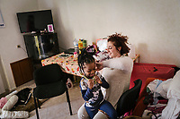 "SUTERA, ITALY - 8 JANUARY 2018: Mariella Cirami (29), who works for the NGO ""I Girasoli"", plays with Blessing, daughter of Nigerian asylum seeker Margareth,  in Sutera, Italy, on January 8th 2018.<br /> <br /> Sutera is an ancient town plastered onto the side of an enormous monolithic rock, topped with a convent, in the middle of the western half of Sicily, about 90 minutes by car south of the Sicilian capital Palermo<br /> Its population fell from 5,000 in 1970 to 1,500 today. In the past 3 years its population has surged  after the local mayor agreed to take in some of the thousands of migrants that have made the dangerous journey from Africa to the Sicily.<br /> <br /> ""Sutera was disappearing,"" says mayor Giuseppe Grizzanti. ""Italians, bound for Germany or England, packed up and left their homes empty. The deaths of inhabitants greatly outnumbered births. Now, thanks to the refugees, we have a chance to revive the city.""<br />  Through an Italian state-funded project called SPRAR (Protection System for Refugees and Asylum Seekers), which in turn is co-funded by the European Union's Fund for the Integration of non-EU Immigrants, Sutera was given financial and resettlement assistance that was co-ordinated by a local non-profit organization called Girasoli (Sunflowers). Girasoli organizes everything from housing and medical care to Italian lessons and psychological counselling for the new settlers.<br /> The school appears to have been the biggest beneficiary of the refugees' arrival, which was kept open thanks to the migrants.<br /> Nunzio Vittarello, the coordinator of the E.U. project working for the NGO ""I Girasoli"" says that there are 50 families in Sutera at the moment."
