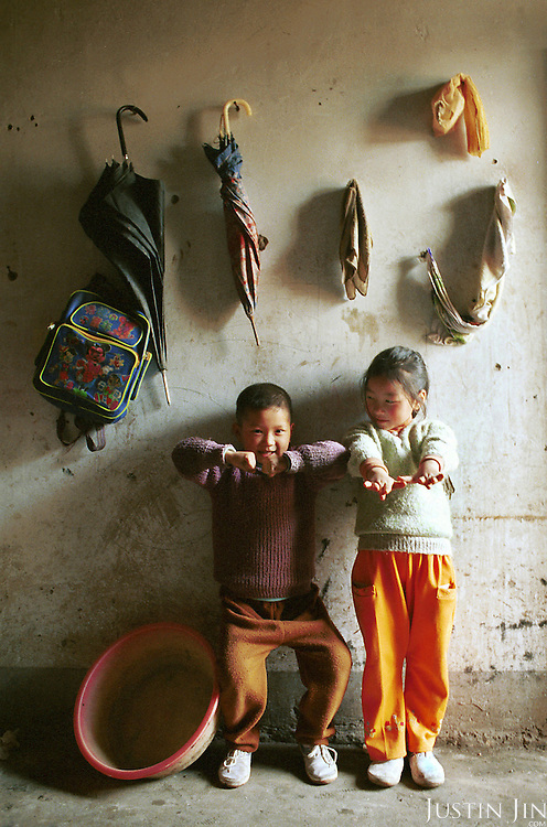 Wei's nephew and niece play in front of a wall where belongings are hung. The household is so poor that it could not afford to buy cabinets and wardrobes...Picture taken April 1999.Copyright Justin Jin