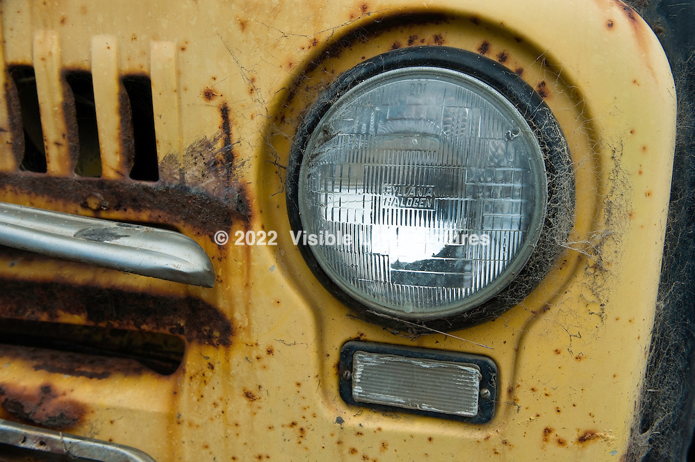 An old, rusted yellow truck headlight.