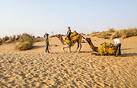 A woman learning how to stay on a camel as it sits down and stands up to let her on and off. Her guides assist with the camels. Thar Desert, Rajasthan, India.