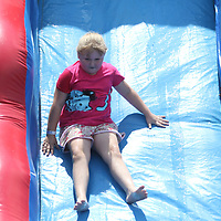 Ella Grace Coker, 7, enjoys one of the many inflatable water slides Saturday at the 8th annual Fourth of July celebration in Guntown