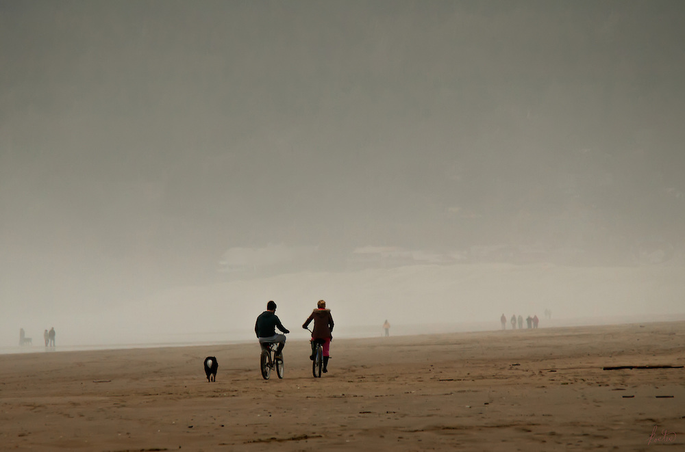 A very foggy twilight is just beginning to set in on this beach in Oregon, but folks are still out walking and this couple are riding bikes as their dog follows along.